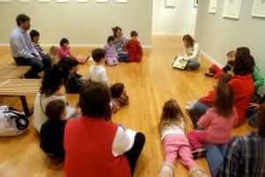 Our Educational Outreach Manager Elena Alvarez shows the children one of Carol Radsprecher's colorful artworks.